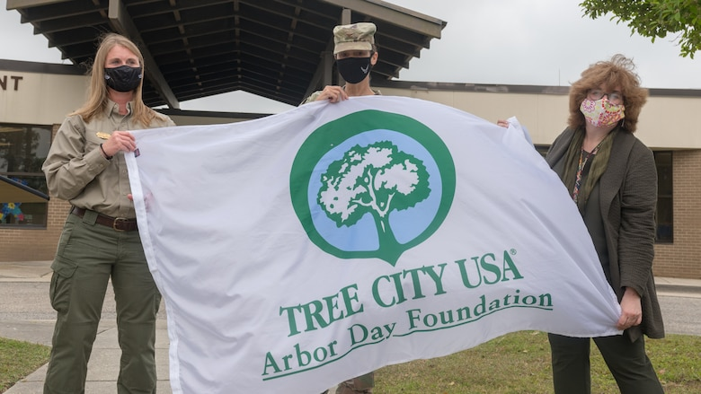 U.S. Air Force Col. Heather Blackwell, 81st Training Wing commander; Meacham Harlow, Mississippi Forestry Commission urban and community forestry partnership coordinator, and Susan Chamberlain, VECTRUS community planner, pose for a photo with the Tree City USA flag during the Arbor Day Celebration in front of the child development center at Keesler Air Force Base, Mississippi, April 30, 2021. A tree planting ceremony also took place at the event. (U.S. Air Force photo by Andre' Askew)