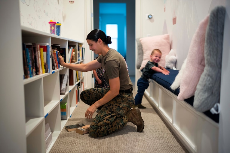 A Marine kneels next to a bookcase as two children stand behind.