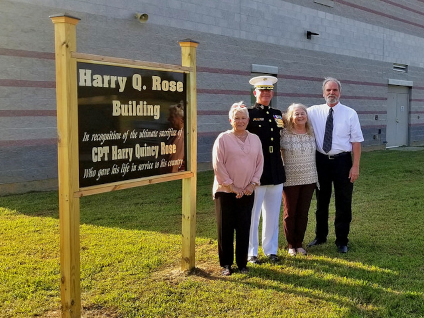 (L-R) Helen Rose Creel, Lt. Col. Harry Gardner, Phyllis Rose Gardner and Albert Lee Creel stand next to the sign commemorating Capt. Harry Q. Rose, Sept. 22, 2018, at the Virginia National Guard's Officer Candidate School building at Fort Pickett, Virginia. (U.S. Army National Guard Photo by Staff Sgt. Matt Lyman)
