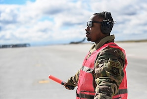 Senior Airman Antoine Barnes, 821st Contingency Response Squadron fire team member, marshals a C-17 Globemaster III from Joint Base Lewis-McChord, Washington, April 27, 2021, on the flight line at Mountain Home AFB, Idaho. Barnes participated in exercise Rainier War, testing his abilities to employ air combat capabilities during a time of potentially imminent foreign aggression. (U.S. Air Force photo by Staff Sgt. Christian Conrad)