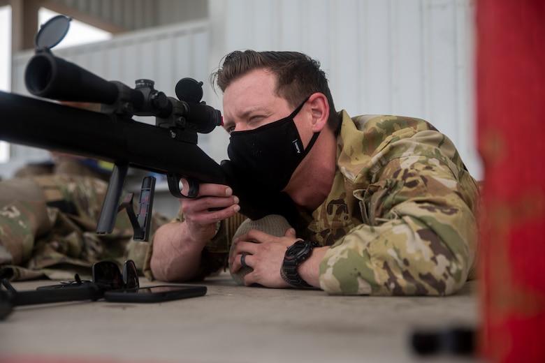 A photo of an Airman aiming a weapon