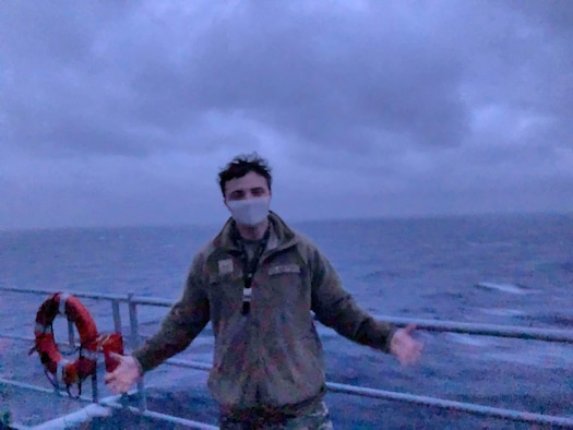 U.S. Air Force Senior Airman Alexander Garrett poses for the camera on the USS Blue Ridge (LCC-19), departing Yokosuka, Japan. The Blue Ridge is responsible for patrolling and fostering relationships within the Indo-Pacific region.  Garrett is the first intelligence analyst from the 3rd Wing to support the Blue Ridge.