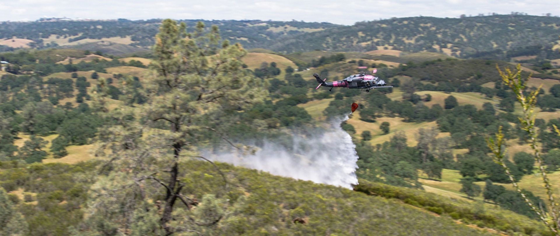 A U.S. Air Force HH-60 Pave Hawk rescue helicopter from the 129th Rescue Wing, California National Guard, deploys its water bucket on a simulated fire during annual joint aerial fire fighting training near Ione, California, April 24, 2021.