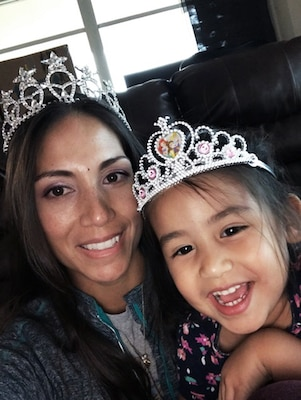 Close up photo of an Hispanic woman and young girl both wearing crowns.