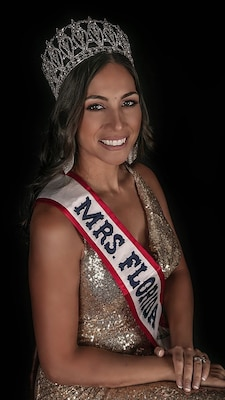 Woman wearing a crown and gold dress with a red, white and blue sash that says Mrs. Florida