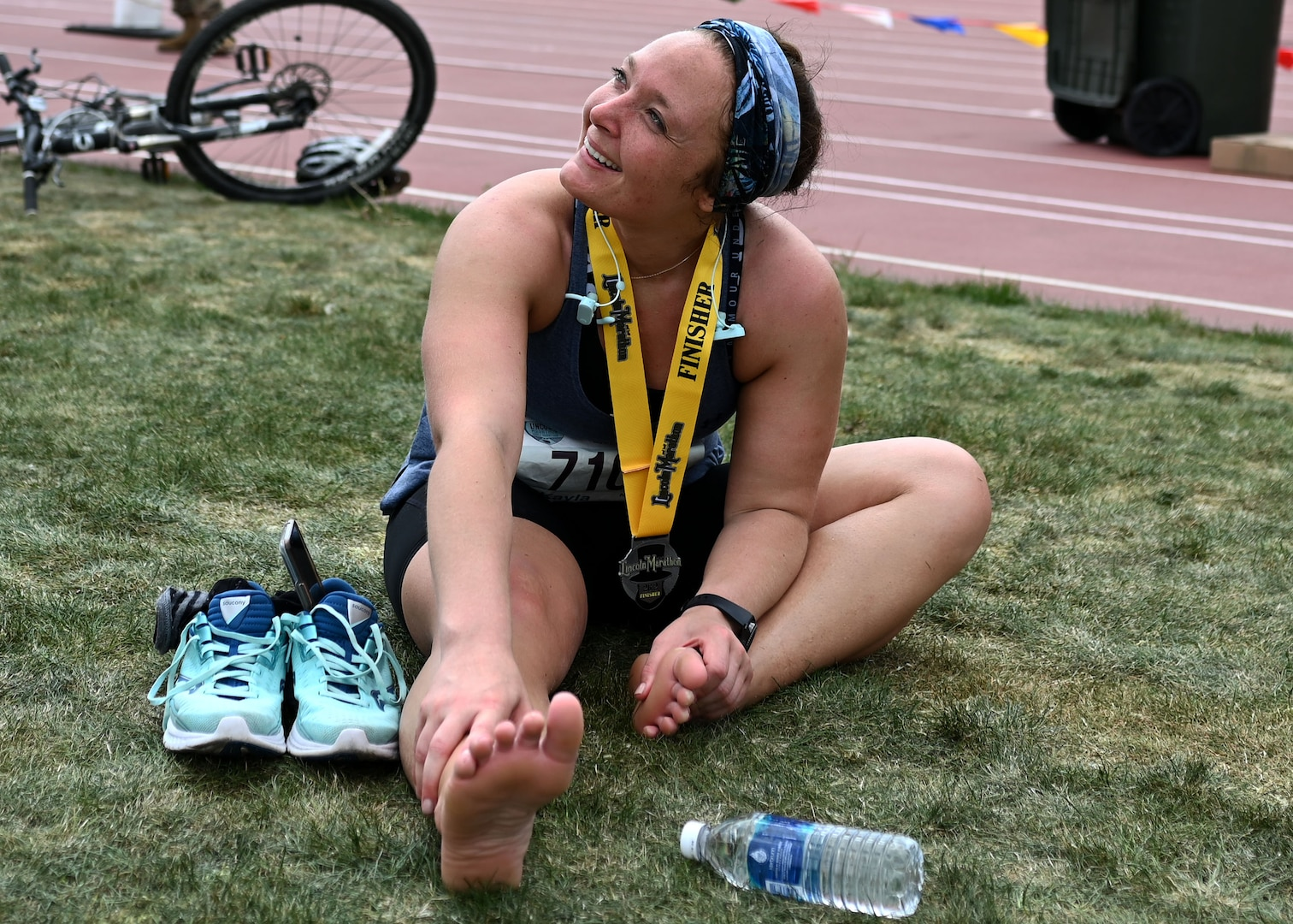 Cpl Kayla Denison of A Battery, 3rd Battalion, 197th Field Artillery Brigade, stretches out at University of Nebraska's Ed Weir Stadium following her May 2 Lincoln Marathon finish in Lincoln, Neb.