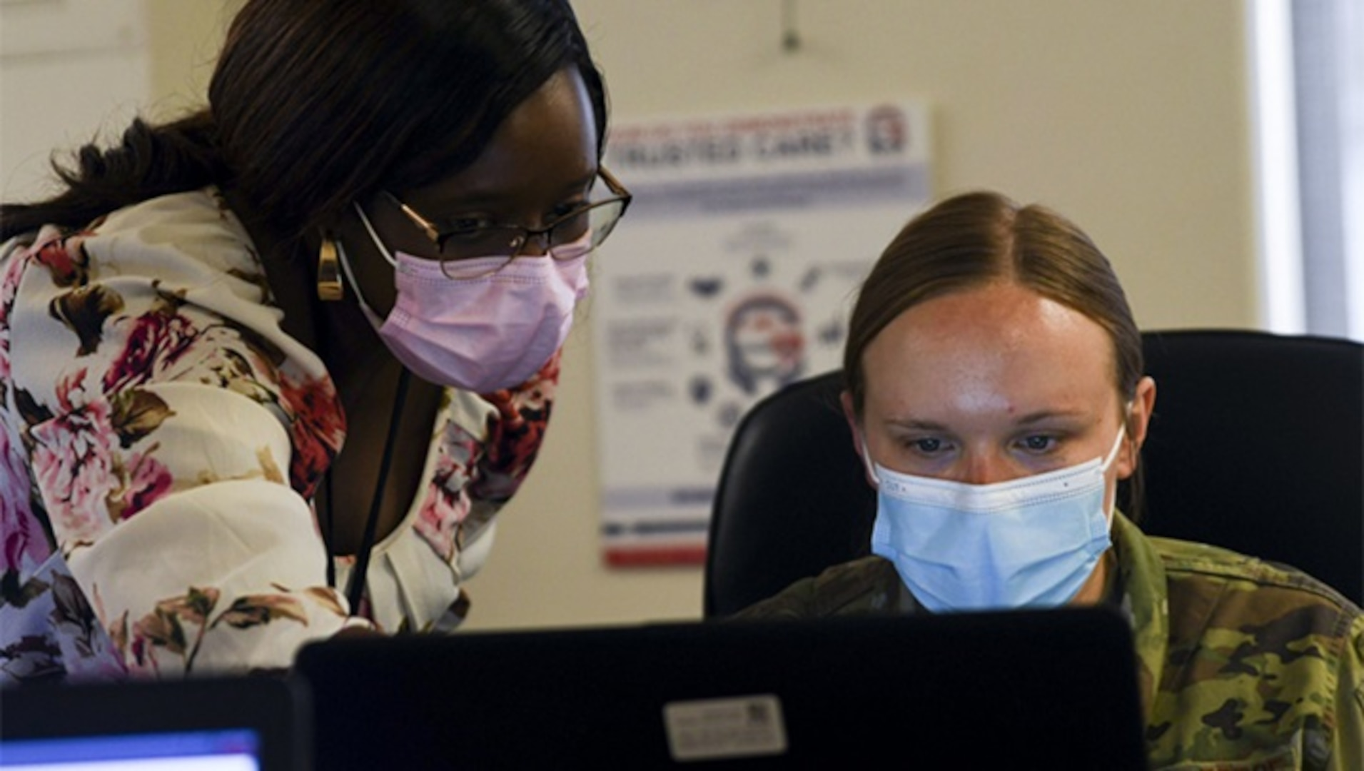 Military Health System MHS GENESIS trainer, gives instruction to Air Force Airman