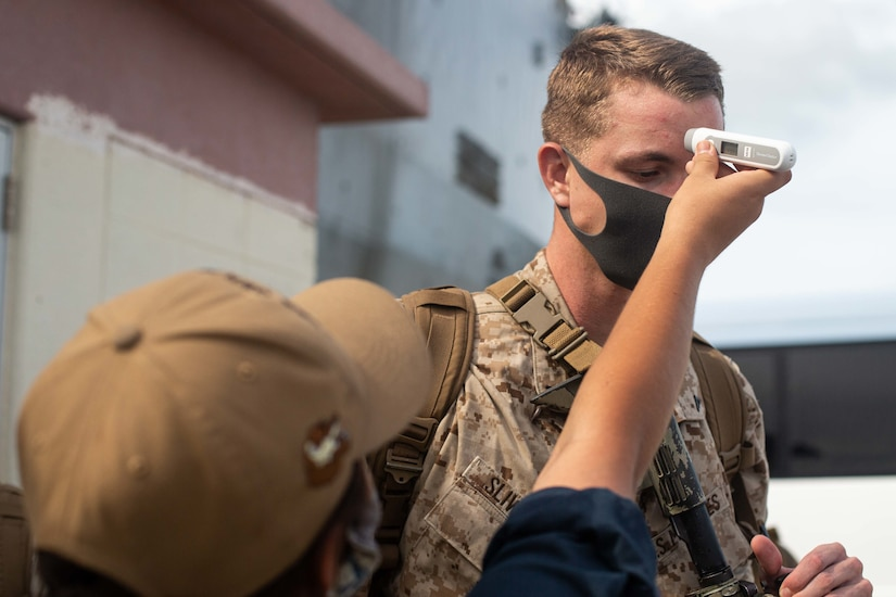 A Marine gets his temperature taken.