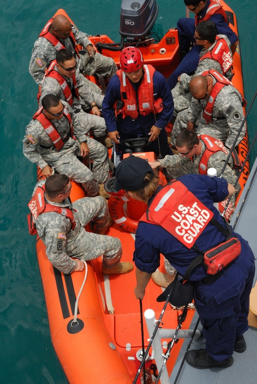 National Guard members board a boat during an exercise.