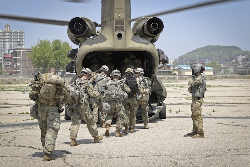 Soldiers board a CH-47 Chinook helicopter.