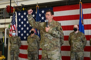 Lt. Gen. Michael A. Loh, director, Air National Guard, raises his fist in the air for emphasis as he speaks into a handheld microphone on a stage with a large US flag in the background at the North Dakota Air National Guard Base, Fargo, N.D., May 2, 2021. Three military members are standing behind him wearing COVID-19 protective masks. Loh is recognizing the three military members for outstanding work in front of an audience that cannot be seen in the photo.