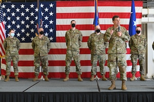 Lt. Gen. Michael A. Loh, director, Air National Guard, speaks into a handheld microphone on a stage in front of five people, all in military uniform wearing COVID-19 protective masks, in front of a large US flag, as he recognizes them for outstanding work at the North Dakota Air National Guard Base, Fargo, N.D., May 2, 2021. They are standing in front of an audience of military members that cannot be seen in the photo.