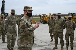 Lt. Gen. Michael A. Loh, director, Air National Guard, stands on a concrete civil engineer training site, among five military members, all in uniform and wearing COVID-19 protective masks at the North Dakota Air National Guard Base, Fargo, N.D., May 2, 2021. Loh is answering questions raised by the military members.