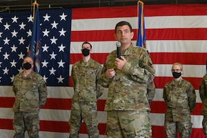 Lt. Gen. Michael A. Loh, director, Air National Guard, speaks using a handheld microphone as he stands on a stage in front of a large U.S. flag, with three Airmen wearing personal protective masks standing behind him. The Airmen are being recognized for outstanding work as they face an audience, which is not visible in the photo, at the North Dakota Air National Guard Base, Fargo, N.D., May 2, 2021.