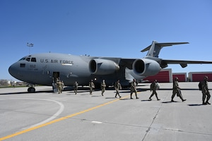 Eleven Airmen in uniform walk across a large concrete aircraft parking area as they get off of a large grey C-17 aircraft upon their return home to the North Dakota Air National Guard Base, Fargo, N.D., May 1, 2021. The Airmen have just completed some military training at base in Mississippi.