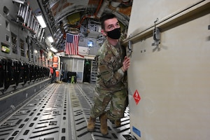 A military member is pushing a large container inside the cargo area of a C-17 aircraft, as he helps unload the cargo container onto the flight line at the North Dakota Air National Guard Base, Fargo, N.D., May 1, 2021.