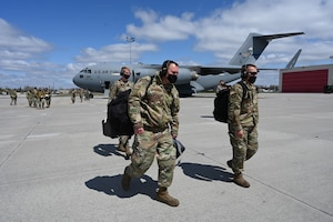 Three military members walk across a large concrete aircraft parking area with a C-17 aircraft in the background at the North Dakota Air National Guard Base, Fargo, N.D., May 3, 2021. The airmen are carrying baggage because they have just arrived there after completing some military training at another location, with several other military personnel visible in the background.