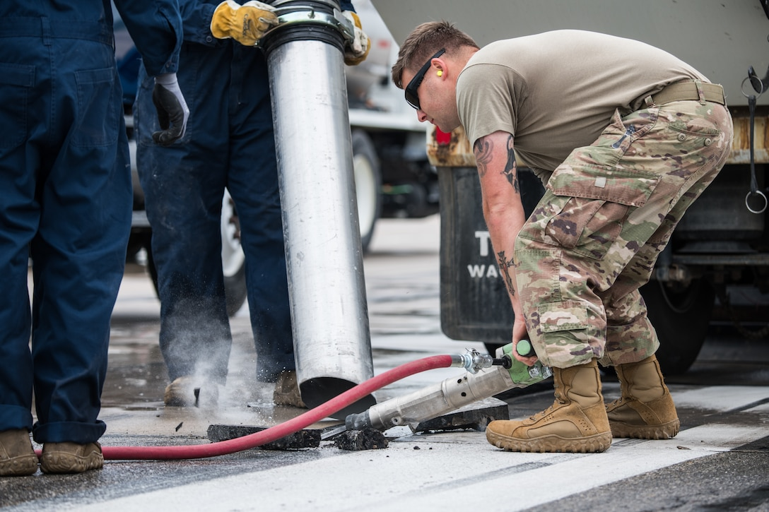 Staff Sgt. Reid Johanna, 22nd Civil Engineer Squadron pavement and heavy machinery craftsman, utilizes a jack hammer during a spall repair on the flightline May 3, 2021, at McConnell Air Force Base, Kansas. Expedient spall repairs quickly repair holes, enabling aircraft to continue to safely land and depart from the flightline. (U.S. Air Force photo by Senior Airman Alan Ricker)