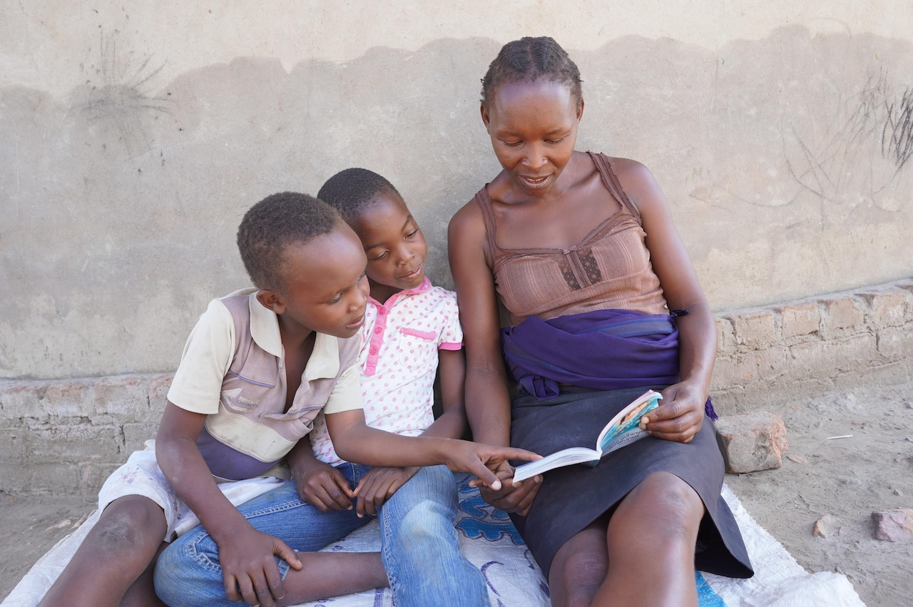 A woman and two children sit on a blanket and look at a book.