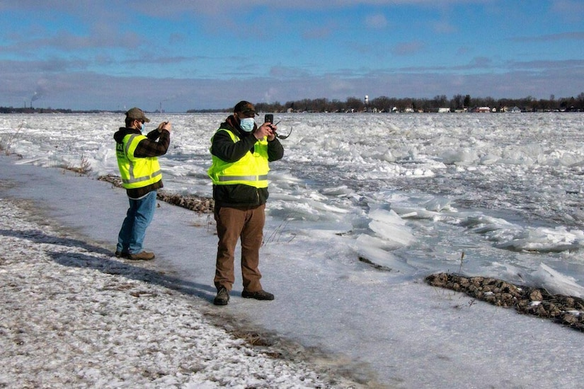 Two men take photos of ice on a river.