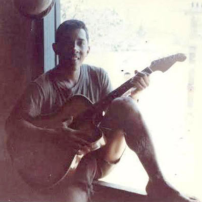 Photo of Lance Cpl. Miguel Keith deployed in Vietnam. Marine is posing with a guitar.