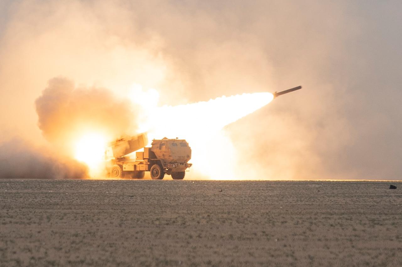 Rockets streaks out of tube on desert range.