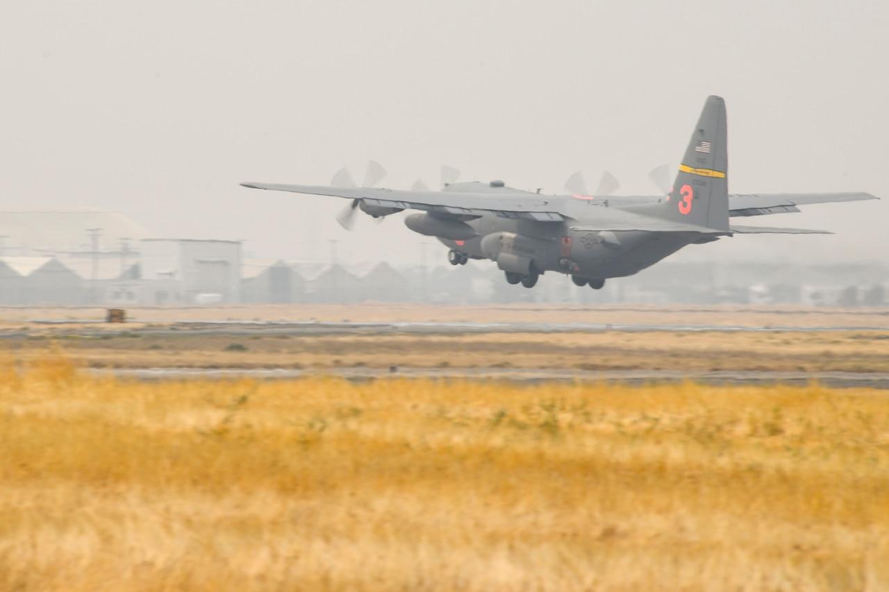 A plane takes off into smoke-shrouded sky.