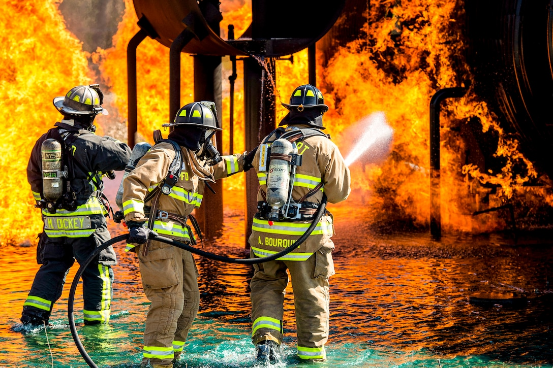 Three firefighters train a hose on an engulfed simulated aircraft.