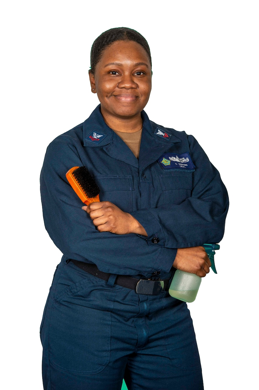 Photo of a Sailor posing with hair brush and spray bottle.