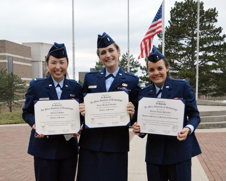 (From left) Second Lieutenants. Michelle McGee, Emily Graves and Jordan Peterson display their Master of Science degrees following the March 25 commencement ceremony at the Air Force Institute of Technology. (U.S. Air Force photo by Katie Scott)