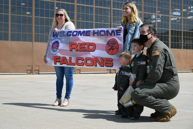 Families of deployers hold a welcome home sign April 13, 2021, at McConnell Air Force Base, Kansas. Members of the 350th Air Refueling Squadron were welcomed home by the open arms of family, friends and colleagues after a 4-month deployment to Al Udeid Air Base, Qatar. (U.S. Air Force photo by Senior Airman Nilsa Garcia)