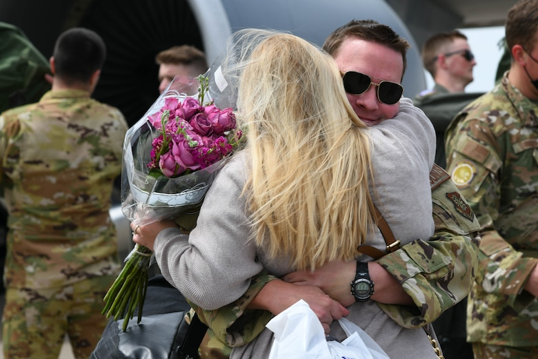 Capt. Micah Newmann, 350th Air Refueling Squadron pilot, hugs his wife Marie Newmann after returning home from deployment April 13, 2021, at McConnell Air Force Base, Kansas. After a demanding yet successful deployment, the Falcons were happy to return home to Team McConnell and their loved ones. (U.S. Air Force photo by Senior Airman Nilsa Garcia)