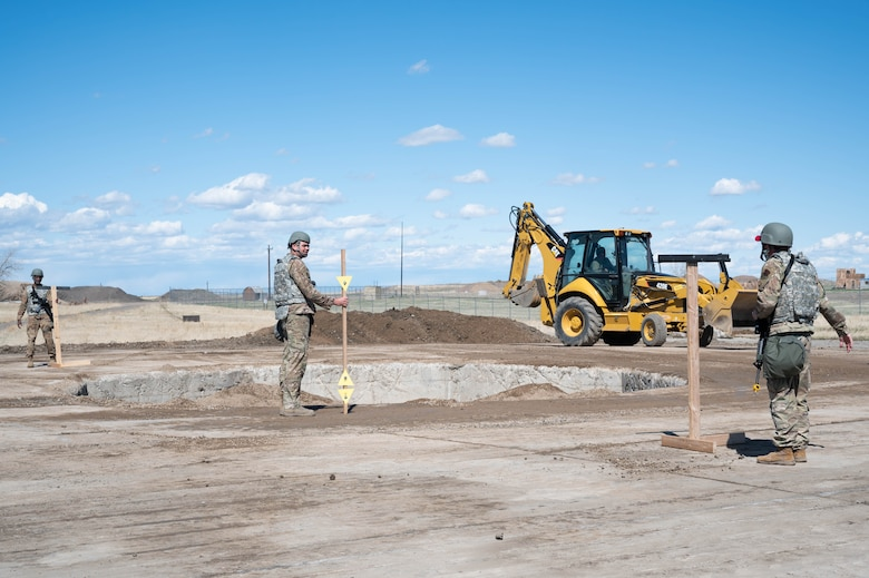 Members of the 819th RED HORSE Squadron perform crater profile measuring by looking between two triangles to check whether the crater is level May 3, 2021, at Malmstrom Air Force Base, Mont.