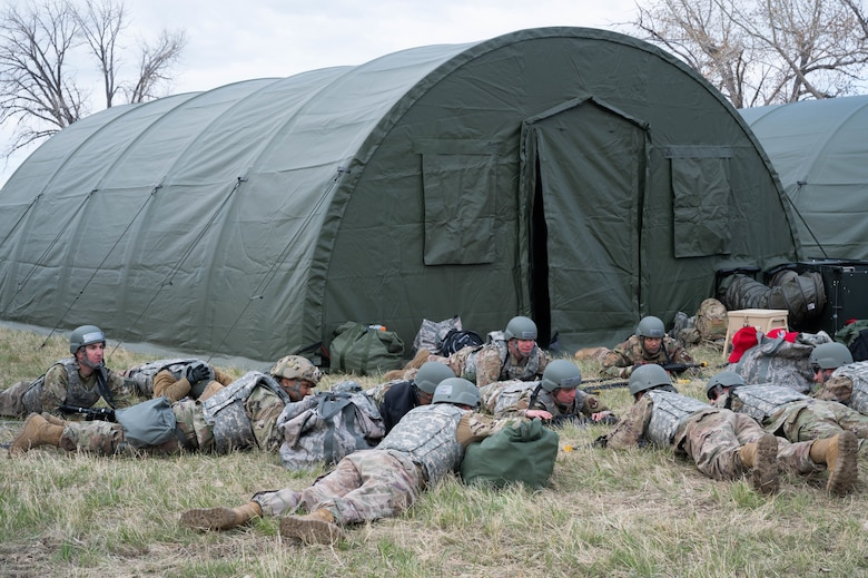 Members of the 819th RED HORSE Squadron lie low to the ground during a simulated attack scenario May 3, 2021, at Malmstrom Air Force Base.