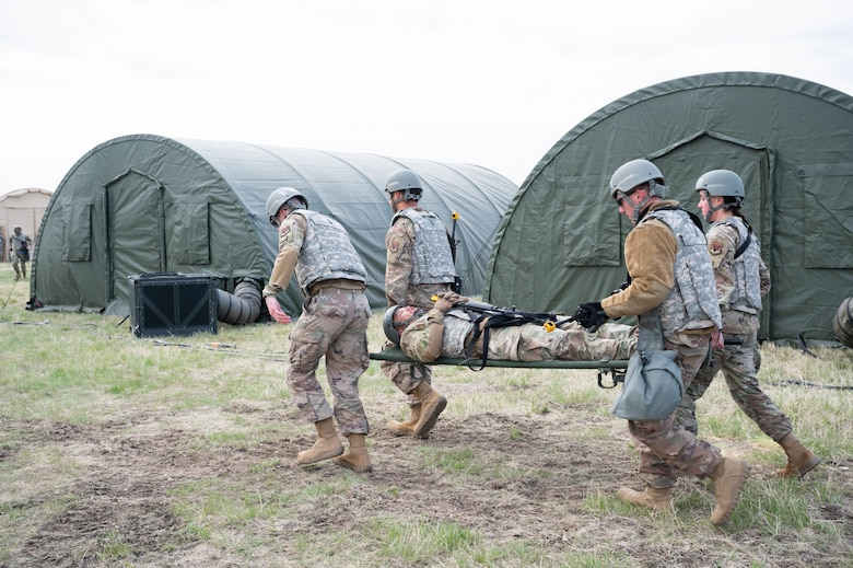 Members of the 819th RED HORSE Squadron carry an Airman on a stretcher to a simulated casualty collection point during an exercise May 4, 2021, at Malmstrom Air Force Base, Mont.