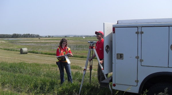 Jennifer Christensen (left) and Larry Morong (retired) survey a levee bank on the Missouri River checking for low spots (levee freeboard) to determine likely areas where overtopping might occur in the event of water level rise. (Courtesy photo)