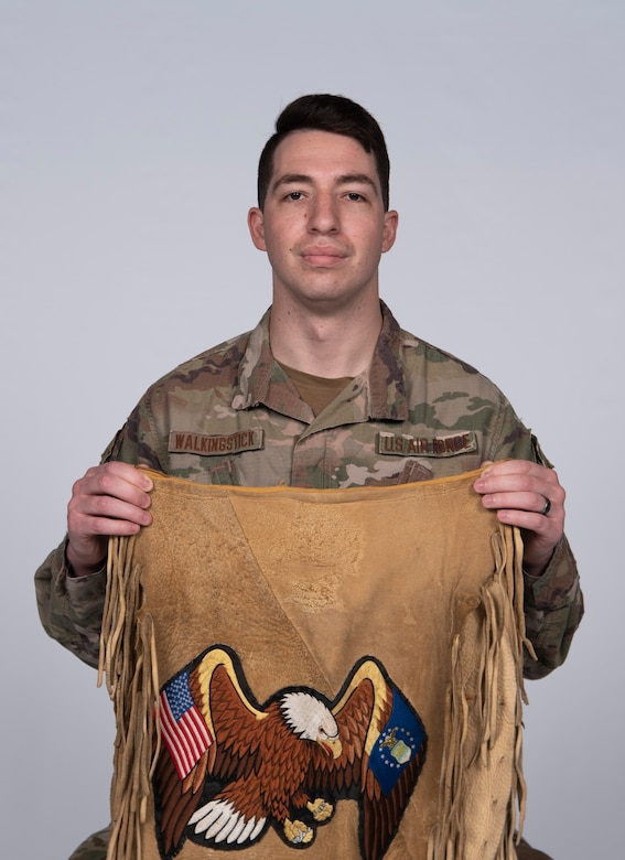U.S. Air Force Senior Airman Taylor Walkingstick, 81st Security Forces Squadron patrolman, presents an apron for a photo at Keesler Air Force Base, Mississippi, April 29, 2021. The apron was handmade by his father, who also served in the military. (U.S. Air Force photo by Senior Airman Kimberly L. Mueller)