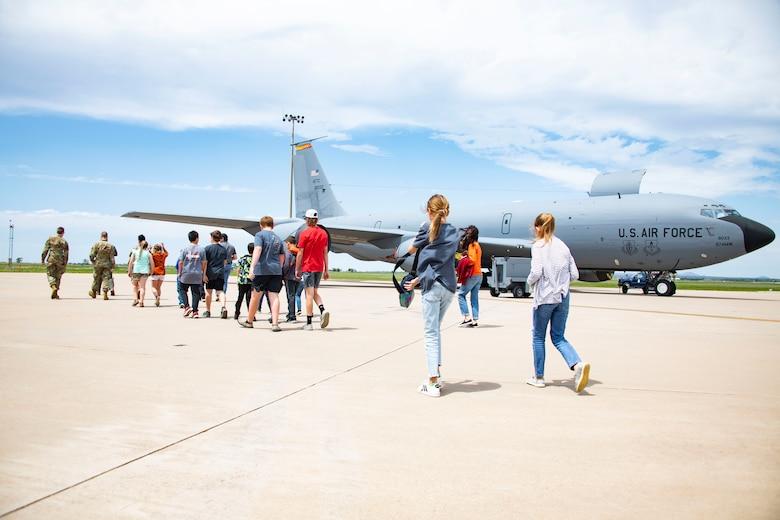 people walk past an aircraft