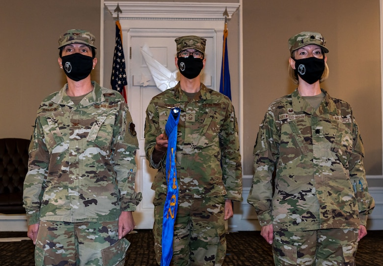 A photo of Airmen standing with a flag.