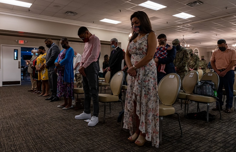 A photo of families bowing their head.
