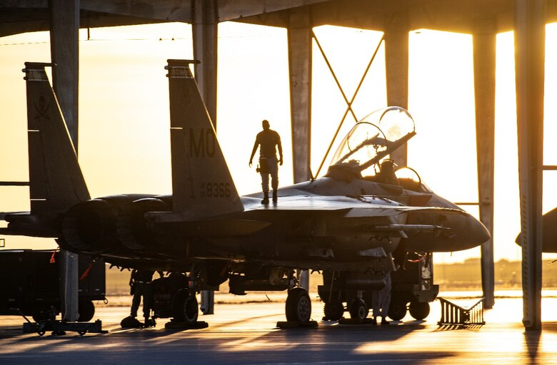 An Airman from Mountain Home Air Force Base, Idaho, surveys an F-15SG Strike Eagle April 28, 2021, on the Mountain Home AFB flight line. The F-15 participated in exercise Rainier War, testing its ability to employ air combat capabilities during a time of potentially imminent foreign aggression.