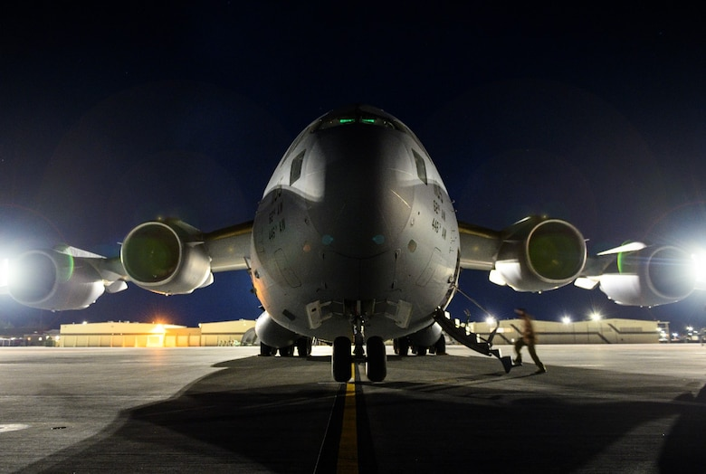 An Airman boards a C-17 Globemaster III from Joint Base Lewis-McChord, Washington, on the flight line at Mountain Home Air Force Base, Idaho, April 27, 2021. The C-17 played a prominent role in exercise Rainier War by ensuring prompt distribution of both defensive and offensive capabilities to simulated areas during the training.