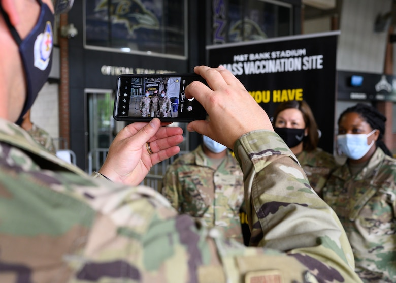 Chief Master Sgt. Paul Muggli, command chief for the 175th Wing, captures a photo of Chief Master Sgt. of the Air Force JoAnne S. Bass with 175th Wing Airmen at the mass vaccination at M&T Bank Stadium, Baltimore, on May 3, 2021.