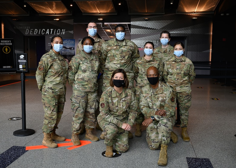 Chief Master Sgt. of the Air Force JoAnne S. Bass poses for a group portrait with Airmen assigned to the 175th Wing, Maryland National Guard, at the mass vaccination site at M&T Bank Stadium, Baltimore, on May 3, 2021.