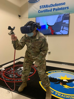 Staff Sgt. Julia Reyna, 318th Training Squadron Structures and Corrosion Instructor, uses the paint simulator during a demonstration at Joint Base San Antonio, Lackland, Texas, April 28, 2021. The newly acquired software allows mobile training teams to travel with the equipment and provide instruction to partner nation members with real-time results while eliminating expenses. (U.S. Air Force photo by Vanessa R. Adame)