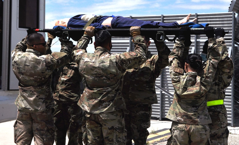 Image of Airmen lifting a stretcher.