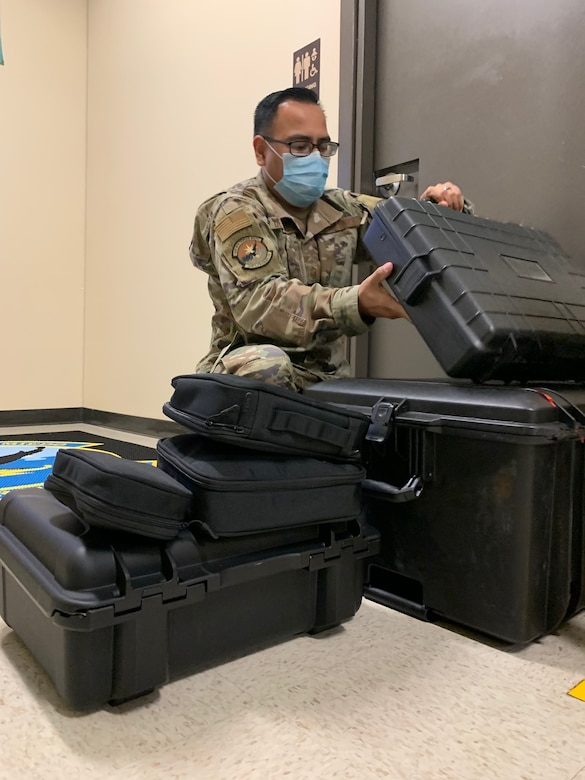 """Master Sgt. Juan De La Rosa, 318th Training Squadron, """"A"""" Flight Chief, sets up the paint simulator at Joint Base San Antonio, Lackland, Texas, April 28, 2021. The newly acquired software allows mobile training teams to travel with the equipment and provide instruction to partner nation members with real-time results while eliminating expenses. (U.S. Air Force photo by Vanessa R. Adame)"""