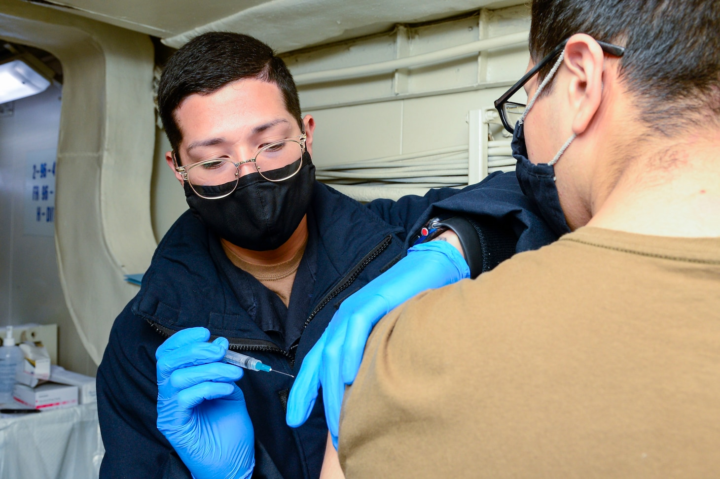 U.S. Navy Hospital Corpsman 3rd Class Adriel Arredondo, from Dallas, left, administers a COVID-19 vaccine to Electrician's Mate Fireman Joseph Brooks, from Jasper, Ga., aboard the aircraft carrier USS Theodore Roosevelt (CVN 71) April 30, 2021.