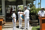A Navy commander accepts a flag from a Navy captaind