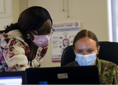 Marion Kimani, Military Health System GENESIS trainer, gives instruction to Airman 1st Class Jenna Slaughter, 355th Mental Health technician, at Davis-Monthan Air Force Base, Arizona, April 7, 2021.